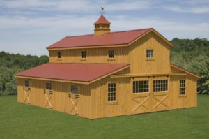 Two story modular horse barn built with natural pine board and batten, center aisle is open with stalls on either side, hay storage area in loft space of horse barn. custom cupola is on roof.